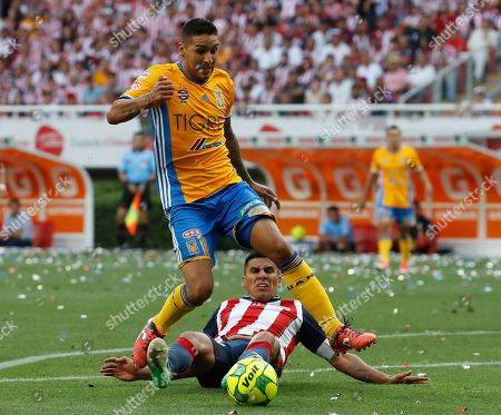 Tigres' Victor Sosa, left, fights for the ball with Chivas' Carlos Salcido during the Mexican soccer league final match in Guadalajara, Mexico