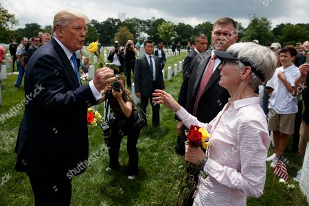 President Donald Trump is handed a rose by Alison Malachowski, whose son Marine Staff Sgt. James M. Malachowski was killed in Afghanistan in 2011, at Section 60 of Arlington National Cemetery, in Arlington, Va
