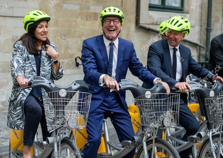 Stock Picture of Paris' mayoress Anne Hidalgo (L), Brussels' Mayor, Yvan Mayeur (C) and the alderman of the sports of Brussels city Alain Courtois (R) take a short bike ride after a press conference for the Tour de France 2019, in Brussels, Belgium, 30 May 2017. The Tour de France 2019 will start in Brussels to mark the 50th anniversary of Merckx' first win at the Tour de France.