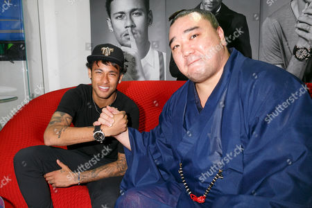 Stock Image of Neymar Jr and Japanese sumo wrestler Harumafuji Kohei, shake hands at GaGa MILANO Harajuku store