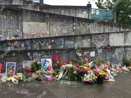 Flowers, candles and chalk tributes are seen, covering a memorial to two men who were fatally stabbed after shielding two young women from an anti-Muslim tirade on a Portland, Ore., light-rail train. Jeremy Joseph Christian, 35, made a first court appearance on charges of aggravated murder and attempted murder Tuesday in a Portland, Oregon courthouse