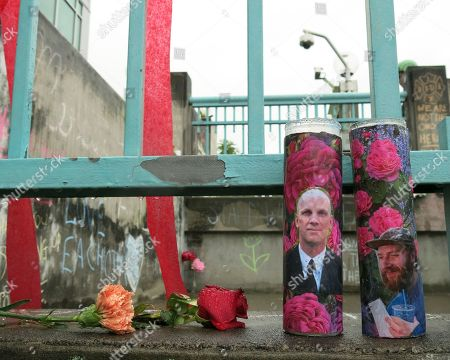 Votive candles bearing the photos of two men who were fatally stabbed on a Portland, Ore., light-train while trying to stop another man from harassing two young women with an anti-Muslim tirade, sit on a rain-soaked memorial on in Portland. Taliesin Myrddin Namkai-Meche, 23, and Ricky Best, 53, died in the attack. The suspect, Jeremy Joseph Christian, 35, made a first court appearance on charges of aggravated murder and attempted murder Tuesday in a Portland, Oregon courthouse