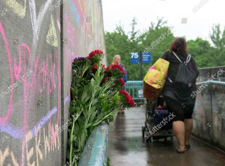 Commuters walk past a rain-soaked memorial, to two men who were fatally stabbed after trying to stop another man who went on an anti-Muslim tirade against two young women on a Portland, Oregon light-rail train. Jeremy Joseph Christian, 35, made a first court appearance on charges of aggravated murder and attempted murder Tuesday in a Portland, Oregon courthouse