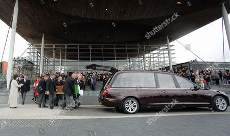 The coffin is carried into a hearse outside the Senedd