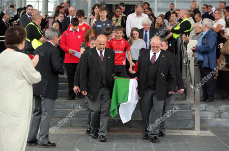 The coffin of Rhodri Morgan draped in a welsh flag is carried outside of the Senedd after the service