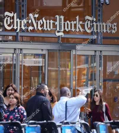 """People walk by The New York Times headquarters, in New York. On Wednesday, May 31, 2017, The New York Times announced it is ditching its """"public editor"""" position that was started in 2003 after the Jayson Blair plagiarism scandal to improve its credibility with readers. The paper will start a """"reader center"""" to interact with readers. It is also launching another round of newsroom buyouts"""