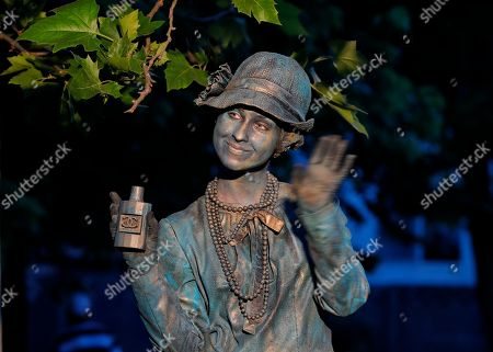 An actress playing a Coco Chanel statue moves her hand during the living statues festival in Bucharest, Romania, . The Living Statues Festival features artists from Austria, the Netherlands and Romania