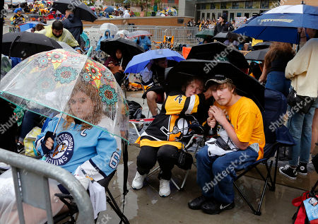 Stock Image of Chris Kunitz, Sidney Crosby, Justin Schultz, Ian Cole From left, Brooke Staudt, of Munhall, Pa., and Maureen Sams and Pierce Sams, of Carnego, Pa., wait in the rain outside PPG Paints Arena before Game 2 of the NHL hockey Stanley Cup Final between the Pittsburgh Penguins and the Nashville Predators, in Pittsburgh