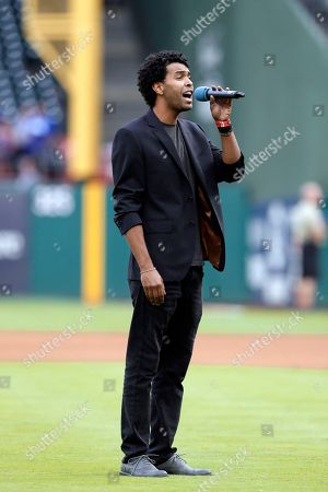 Singer Aquile sings the national anthem before a baseball game between the Tampa Bay Rays and Texas Rangers, in Arlington, Texas