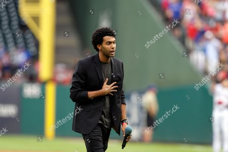 Singer Aquile acknowledges applause after singing the national anthem before a baseball game between the Tampa Bay Rays and Texas Rangers, in Arlington, Texas