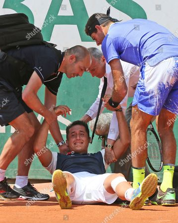 Spain's Nicolas Almagro is helped by Argentina's Juan Martin del Potro after he collapsed with a left knee injury in his second round match against at the French Open tennis tournament at the Roland Garros stadium, in Paris, France. . Almagro was unable to continue to play