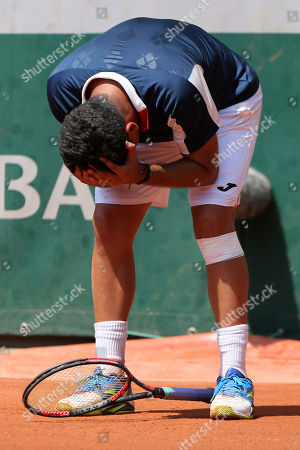 Spain's Nicolas Almagro grabs his head prior to collapsing with a left knee injury in his second round match against Argentina's Juan Martin del Potro at the French Open tennis tournament at the Roland Garros stadium, in Paris, France. . Almagro was unable to continue