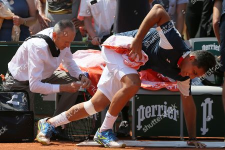 Spain's Nicolas Almagro tries to ge back on his feet after being treated for a left knee injury in his second round match against Argentina's Juan Martin del Potro at the French Open tennis tournament at the Roland Garros stadium, in Paris, France. . Almagro was unable to continue to play