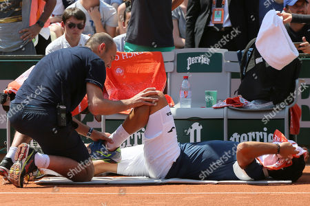 Spain's Nicolas Almagro is treated for a left knee injury in his second round match against Argentina's Juan Martin del Potro at the French Open tennis tournament at the Roland Garros stadium, in Paris, France. . Almagro was unable to continue to play