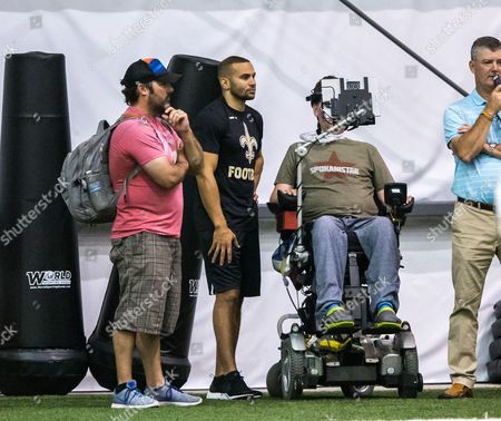 Former Saints wide receiver Lance Moore (in black) standing on the sidelines with Steve Gleason (blue jeans) in action during the organized team activities at the New Orleans Saints Training Facility in Metairie, LA