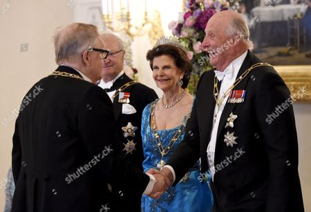 Former Finnish President and Nobel Peace Prize winner Martti Ahtisaari and King Harald V of Norway shaking hands and King Carl Gustaf of Sweden and Queen Silvia of Sweden are smiling in the background,