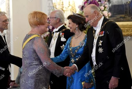 Former Finnish President Tarja Halonen (front left) and King Harald V of Norway shaking hands and behind them are Halonen's husband Pentti Arajarvi shaking hands with King Carl Gustaf of Sweden and Queen Silvia of Sweden,