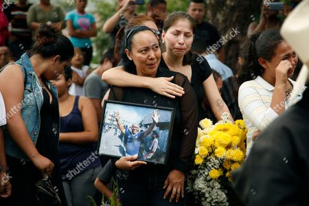 Stock Picture of Gladiz Zuniga holds a photograph of her father, soccer fan Jose Zuniga, during his burial in Tegucigalpa, Honduras. Thousands of fans trying to force their way into a stadium for a soccer championship between Motagua and Honduras Progreso stampeded in panic when police fired tear gas Sunday, leaving at least four people dead
