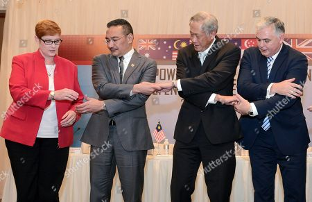 From left, Australian Defense Minister Marise Payne, Malaysian Defense Minister Hishammuddin Hussein, Singapore's Defense Minister Ng Eng Hen, New Zealand Defense Minister Mark Mitchell link hands as they pose for a photograph at a joint press conference at the Five Power Defense Arrangements Defense Ministers Meeting in Singapore