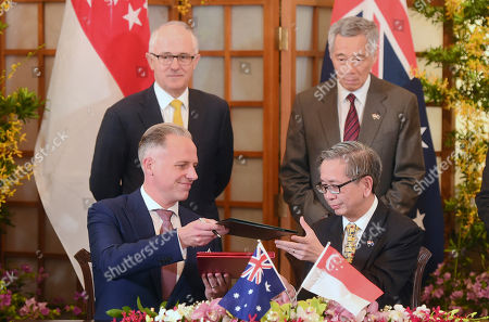 Stock Image of Malcolm Turnbull, Tobias Feakin, David Koh, Lee Hsien Loong Tobias Feakin, Australian Ambassador for Cyber Affairs, Department of Foreign Affairs and Trade, bottom left, signs a memorandum of understanding with David Koh, Chief Executive of Singapore's Cyber Security Agency as Australian Prime Minister Malcolm Turnbull, top left, and Singapore's Prime Minister Lee Hsien Loong, top right, look on at the Istana or Presidential Palace in Singapore on . Turnbull is in the city-state for a 3-day official visit