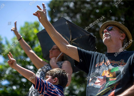 Mourners hold up peace signs during Gregg Allman's burial at Rose Hill Cemetery, in Macon, Ga. Family, friends and fans gathered to say goodbye to music legend Gregg Allman, who died over the Memorial Day weekend at the age of 69