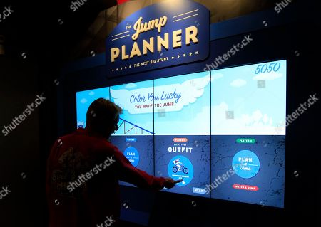 A member of the museum staff demonstrates the Jump Planner at the Evel Knievel Museum in Topeka, Kan., . Visitors can pick the leathers, cycle, ramp angle and speed of a jump. The planner shows if the jump would work