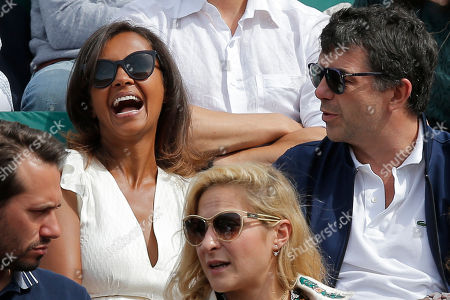 Karine Le marchand and Stephane Plaza joke as the watch Timea Bacsinszky of Switzerland and Venus Williams of the U.S. during their fourth round match of the French Open tennis tournament at the Roland Garros stadium, in Paris, France