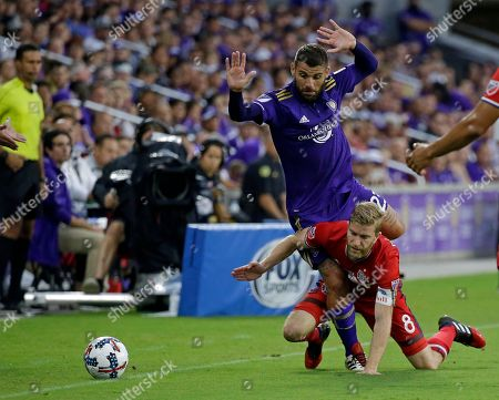 Orlando City's Antonio Nocerino, top gets tangled up with Chicago Fire's Michael de Leeuw (8) during the first half of an MLS soccer game, in Orlando, Fla