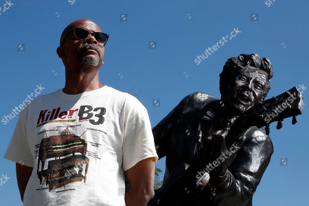 """Charles Berry Jr., son of rock 'n' roll legend Chuck Berry, poses alongside a statue of his late father, in University City, Mo. Berry Jr. plays guitar on his father's final album entitled """"Chuck"""", a 10-song set nearly four decades in the making"""