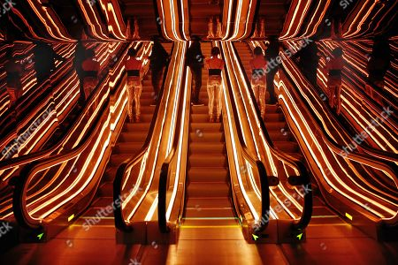 An optical illusion of a single escalator, center, in the lobby of the PUBLIC hotel, is created by its reflective surroundings, in New York, . The new hotel opening Wednesday, June 7, 2017, on Manhattan's Lower East Side is the latest project from Ian Schrager, who's known for introducing the concept of boutique hotels and as co-founder of the legendary disco Studio 54