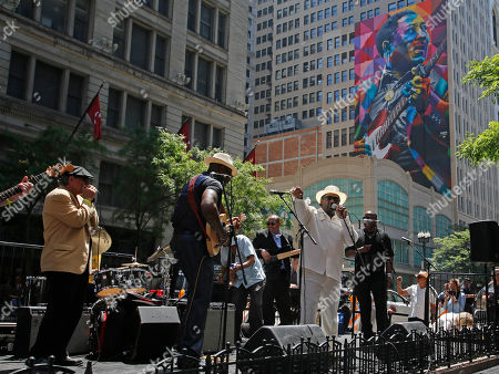 Mud Morganfield, son of Muddy Waters, in white, and former band members, perform for the dedication of the mural of blues music legend Muddy Waters, in Chicago. The mural was created by Brazilian street artist, Eduardo Kobra and dedicated before the city's annual blues festival this weekend