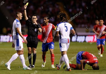 Costa Rica's Johan Venegas kneels on the field after being fouled by Panama's Valentin Pimentel, left, as U.S. referee Jair Marrufo shows him a yellow card during a 2018 Russia World Cup qualifying soccer match at the National stadium in San Jose, Costa Rica, . At center left is Costa Rica's Bryan Ruiz and at center right is Panama's Roman Torres