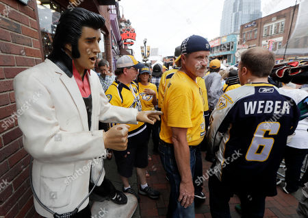 People in Nashville Predators shirts pass an Elvis Presley statue on Broadway before Game 4 of the NHL hockey Stanley Cup Finals between the Predators and the Pittsburgh Penguins on Broadway in Nashville, Tenn. The Predators host Game 6 on Sunday evening at the same time that the annual CMA Music Festival holds its concert headlined by Keith Urban and Brad Paisley. The honky-tonk lined blocks in between the two venues are expected to packed with even more fans, and city officials expect a total of 100,000 people to throng the downtown streets