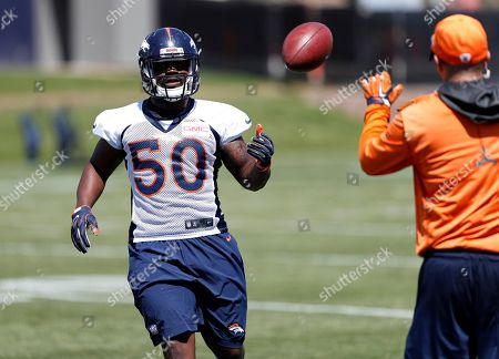 Graph, Denver Broncos inside linebacker Zaire Anderson, left, tosses the ball to a coach during the team's NFL football minicamp session in Englewood, Colo. Anderson is happy to be back on the gridiron after he was knocked unconscious while covering a punt against the Oakland Raiders and then carted off the field