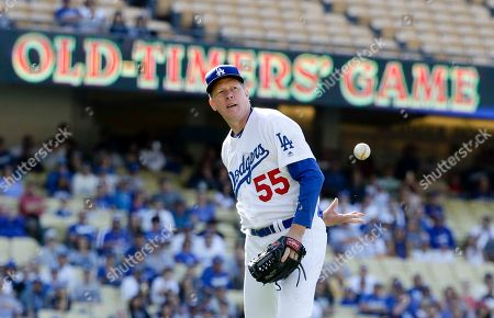 Former Los Angeles Dodgers pitcher Orel Hershiser throws the ball to first behind back during the first inning of an old-timers baseball game in Los Angeles