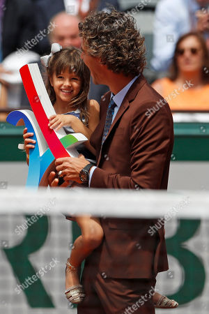 Former Brazilian tennis ace Gustavo Kuerten carries a sign in support of the 2024 Paris2024 Olympic bid before Spain's Rafael Nadal plays Switzerland's Stan Wawrinka in their final match of the French Open tennis tournament at the Roland Garros stadium, in Paris