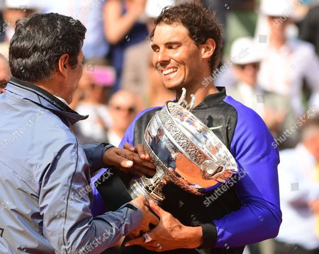 Rafael Nadal of Spain gets his trophy from his uncle Toni Nadal after winning the men?s singles final match against  Stanislas Wawrinka of Switzerland during the French Open tennis tournament at Roland Garros in Paris, France, 11 June 2017.