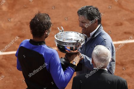 Rafael Nadal (L) of Spain receives his trophy from his uncle Toni Nadal (R) after winning the Men?s singles final match against Stanislas Wawrinka of Switzerland during the French Open tennis tournament at Roland Garros in Paris, France, 11 June 2017.