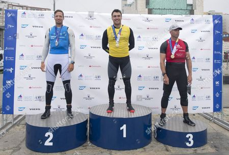 Stock Image of British Ben Cornish (C) celebrates his victory next to Hungarian Zsombor Berecz (L) second and British Edward Wright (R) third in the Finn category during the Sailing World Cup final held in Santander, Spain, on 11 June 2017.