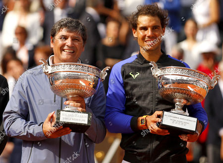 Uncle Toni Nadal stands next to Rafael Nadal with the La Decima trophy following the Mens Final