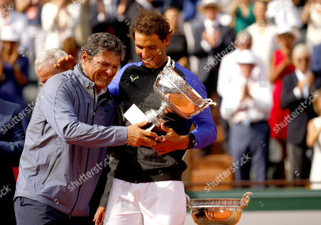 Uncle Toni Nadal hugs Rafael Nadal with the La Decima trophy following the Mens Final