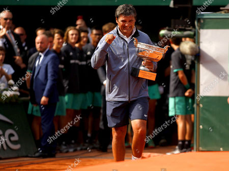 Uncle Toni Nadal carries on the La Decima trophy to give to Rafael Nadal of Spain following the Mens Final