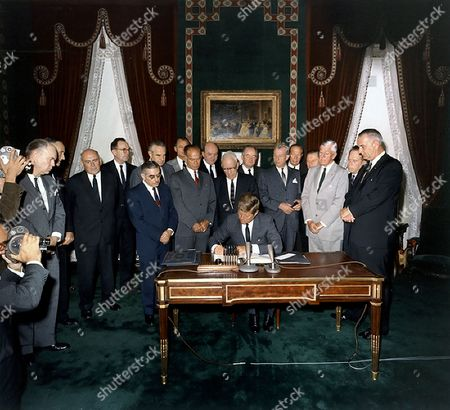 United States President John F. Kennedy signs the Limited Nuclear Test Ban Treaty in the White House Treaty Room on October 7, 1963. From left to right: William Hopkins, U.S. Senator Mike Mansfield (Democrat of Montana), John J. McCloy, Adrian S. Fisher, U.S. Senator John Pastore (Democrat of Rhode Island), W. Averell Harriman, U.S. Senator George Smathers (Democrat of Florida), U.S. Senator J.W. Fulbright (Democrat of Arkansas), U.S. Secretary of State Dean Rusk,  U.S. Senator George Aiken (Republican of Vermont), President Kennedy, U.S. Senator Hubert H. Humphrey (Democrat of Minnesota),  U.S. Senator Everett Dirksen (Republican of Illinois), William C. Foster, U.S. Senator Howard W. Cannon (Democrat of Nevada), U.S. Senator Leverett Saltonstall (Republican of Massachusetts), U.S. Senator Thomas H. Kuchel (Republican of California), U.S. Vice President Lyndon B. Johnson. White House, Treaty Room