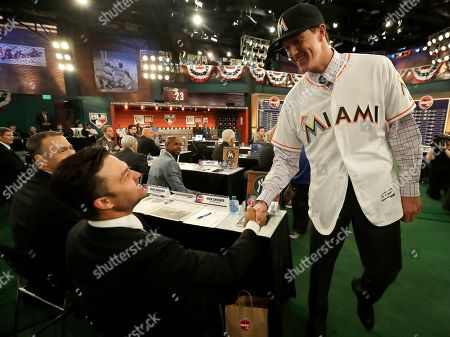 Trevor Rogers, a pitcher from Carlsbad High School in Carlsbad, N.M., right, shakes hands with former New York Yankees player Nick Swisher after being selected No. 13 by the Miami Marlins in the first round of the Major League Baseball draft, in Secaucus, N.J