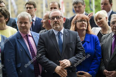 Stewart Hosie MP (centre) watches as SNP leader Nicola Sturgeon holds a photocall and press conference outside parliament with her newly elected MPs. Over the weekend British prime minister Theresa May formed a new cabinet and continues discussions with the DUP in an attempt to form a new government.