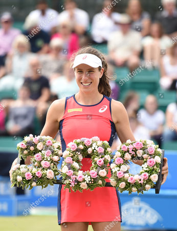 Johanna Konta of Great Britain after winning the Women's first round match of the Aegon Open against Tara Moore of Great Britain is presented with flowers after winning 300 tour wins