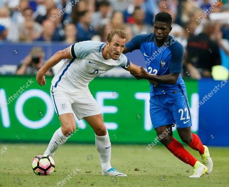 England's Harry Kane, left, challenges France's Samuel Umtiti during a friendly soccer match between France and England at the Stade de France in Saint Denis, north of Paris, France
