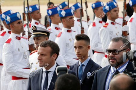 Morocco's King Mohammed VI, right, followed by his son Crown Prince Moulay El Hassan, center, welcomes French President Emmanuel Macron, left, upon his arrival at Rabat airport, Morocco, . The visit is the first by the recently elected French president to a North African country and aims to strengthen the relationship between France and Morocco, including cooperation on security issues