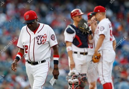 Stock Photo of Dusty Baker, Joe Blanton, Jose Lobaton Washington Nationals manager Dusty Baker (12) walks off the field after pulling relief pitcher Blake Treinen and putting in relief pitcher Joe Blanton during the eight inning of a baseball game against the Atlanta Braves at Nationals Park, in Washington. The Braves won 13-2. Behind Baker, catcher Jose Lobaton (59) talks with relief pitcher Joe Blanton (56) on the mound
