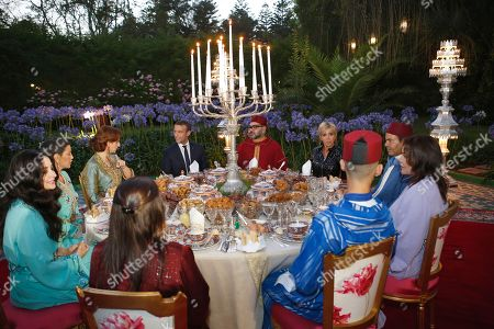 In this photo dated Morocco's King Mohammed VI, center right, his wife Princess Lalla Salma, background left, French President Emmanuel Macron, center left, and his wife Brigitte Macron, background right, attend an Iftar meal, the evening meal when Muslims end their daily Ramadan fast at sunset, at the King Palace in Rabat, Morocco. Clockwise from left : Princess Lalla Oum Kaltoum, Princess Lalla Salma, Crown prince Moulay Hassan, Princess Lalla Hasnaa, Prince Moulay Rachid, Brigitte Macron, King Mohammed VI, Emmanuel Macron, Princess Lalla Salma, Princess Lalla Meryem